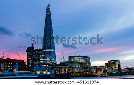 LONDON, UNITED KINGDOM - FEBRUARY 20, 2015: The Shard skyscraper spire at dusk as night approaches over lighted buildings at the Thames river riverside with the guarding form of the Belfast warship. - stock photo