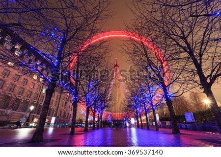 LONDON, UNITED KINGDOM â?? 24 JANUARY 2016: Long exposure of London Eye with red light and blue lighting decoration on trees. At a height of 135m, it is the tallest Ferris wheel in Europe. - stock photo