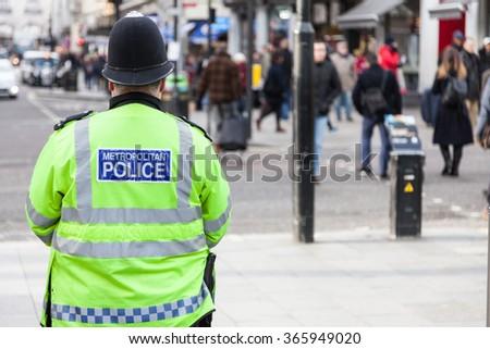 LONDON, UNITED KINGDOM - JANUARY, 2016: Policeman watching people on streets of London - stock photo