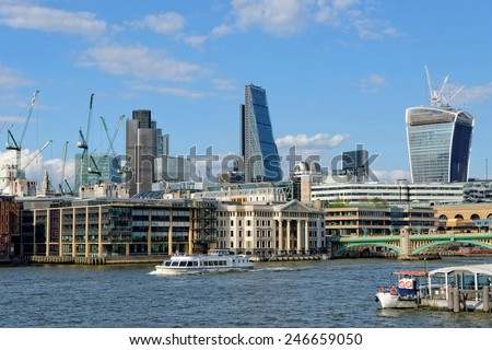 LONDON, UNITED KINGDOM - JULY 1, 2014: A City Cruises tour boat sails on the Thames River near Southwark Bridge. Thames is the longest river in England with 346 km (215 miles) long. - stock photo