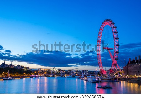 LONDON, UNITED KINGDOM - JULY 28 2015: The London Eye on the edge of the Thames River provides a great vantage point over central London