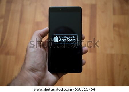 London, United Kingdom, june 5, 2017: Man holding smartphone with Apple app store logo on the screen. Laminate wood background.