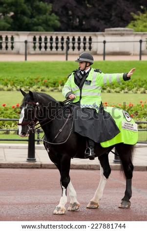 London, United Kingdom - June 11, 2010: Policeman on the horse patrols near Buckingham Palace in front of a crowd waiting for guard change ceremony. - stock photo