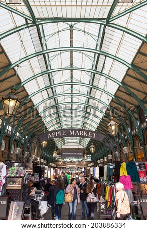 LONDON, UNITED KINGDOM - JUNE 14, 2014: Tourists and shoppers visiting Apple Market, in Covent Garden. One of the main London attractions, Covent Garden is visited by over 30 million people a year. - stock photo