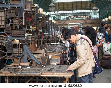 LONDON, UNITED KINGDOM - June 15 2015: Visitors in Apple Market in Covent Garden in London, UK. The Apple Market is sells arts and crafts dedicated to antiques and collectable  items. - stock photo
