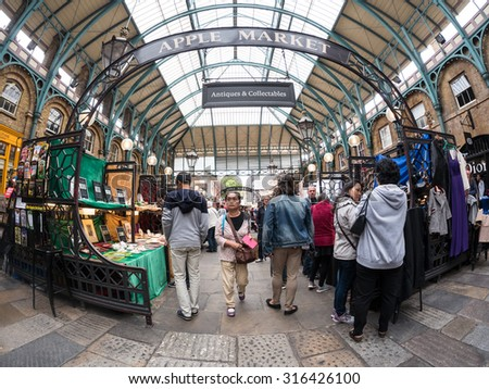 LONDON, UNITED KINGDOM - June 15 2015: Visitors in Apple Market in Covent Garden in London, UK. The Apple Market is sells arts and crafts dedicated to antiques and collectables items. - stock photo