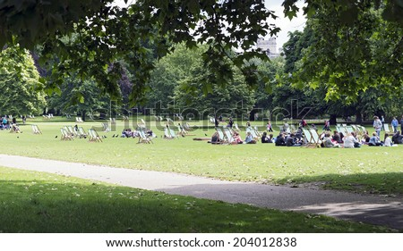 LONDON, UNITED KINGDOM - JUNE 5, 2014: Young people talking and relaxing in St James's Park, during a warm Spring morning