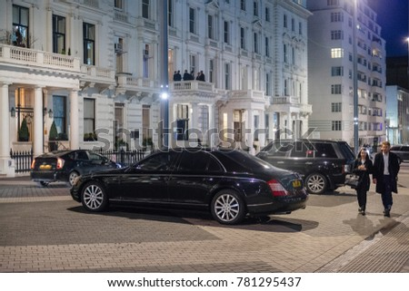 LONDON, UNITED KINGDOM - MAR 9 2017: British pedestrians walking next to Mercedes-Maybach luxury limousine parked on the Exhibition Rd, Kensington London.