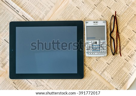 LONDON, UNITED KINGDOM - MARCH 20, 2014: Modern iPad Tablet computer and old QWERTY smartphone above the Financial Times magazine with worldwide stock and vision eye wear glasses