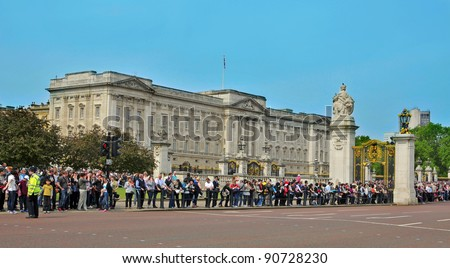 LONDON, UNITED KINGDOM - MAY 6: A crowd waits for the Changing of the Guard in Buckingham Palace on May 6, 2011 in London, UK. This is one of most important attraction for visitors in London - stock photo
