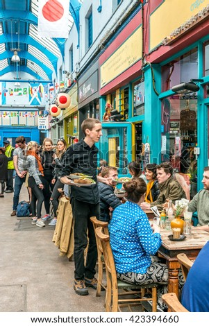 London, United Kingdom - May 14, 2016: Brixton Village and Brixton Station Road Market. Colorful and multicultural community market run by local traders in South London. Restaurants - stock photo