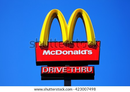 London, United Kingdom, May 27, 2012 : McDonald's yellow and red drive-thru logo advertising sign placed on a pole with a clear blue sky - stock photo
