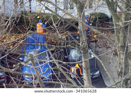 London, United Kingdom - November 18, 2015: Leaves are swept into piles which are then picked up by a council truck. A gang of council street cleaners work together to get the job done.