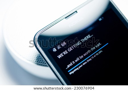 LONDON, UNITED KINGDOM - NOVEMBER 9: Nokia Lumia smartphone windows phone with We're Getting There migrating data status bar percentage. Microsoft has announced that it will stop using Nokia branding - stock photo