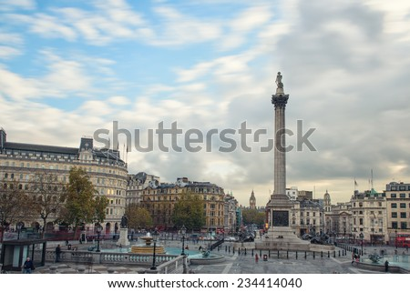 LONDON UNITED KINGDOM - NOVEMBER 18 , 2014: Tourists visit Trafalgar Square on a cloudy day. It's one of the most popular attraction in London, often considered the heart of London. November 18 , 2014 - stock photo