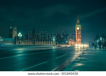 LONDON, UNITED KINGDOM - OCTOBER 9, 2014:  Night view of Big Ben across with Westminster Bridge on a damp night with cars and people crossing. - stock photo