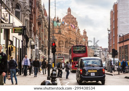 LONDON, UNITED KINGDOM - OCTOBER 8, 2014:  Street view of London along busy Brompton Road in London with Harrods and iconic double decker bus.  - stock photo