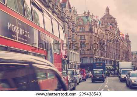 LONDON, UNITED KINGDOM - OCTOBER 8, 2014:  Vintage style street view of London along busy Brompton Road in London with Harrods and iconic double decker bus.  - stock photo