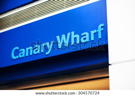 LONDON, UNITED KINGDOM - SEP 1, 2013: Canary Wharf sign in the named business district of London on the River Thames, is surrounded by the three tallest buildings in the United Kingdom.