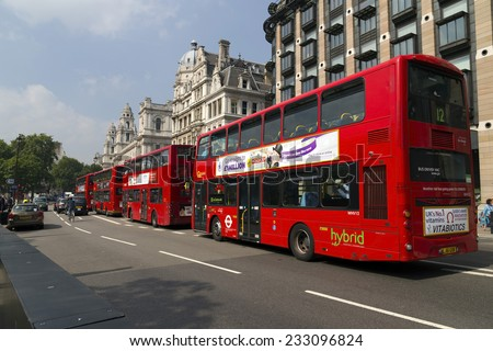 London, United Kingdom September 4, 2013: 4 Double decker London buses waiting in the traffic lights next to Big Ben. Closest one is a Hybrid model. - stock photo