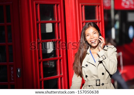 London woman taking on smart phone by red phone booth. Young casual female business woman walking with mobile phone smartphone in London, England, United Kingdom. Multiracial Asian Caucasian model. - stock photo