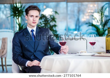 Lone businessman in a bar. Confident businessman in formal wear sitting at a table in a restaurant while holding a glass of wine and looking ahead - stock photo