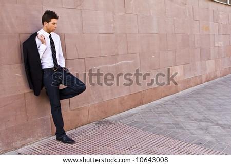 Lone businessman posing on wall - stock photo