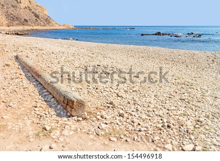 Lone dry log on rocky shore. Wide angle, low perspective view, rocky beach on a bright sunny day. Old weathered wood log in foreground. Hillside, ocean, clear blue sky in background. Horizontal scene. - stock photo