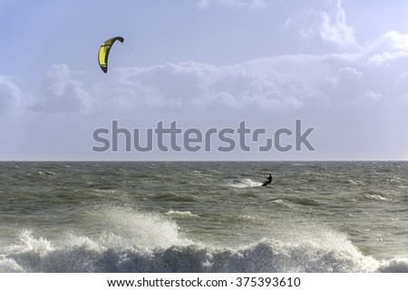 Lone figure kite surfing on a windy day in the Solent off the south coast of England at Hayling Island. The rough conditions are emphasized by the blurred spray in the foreground.