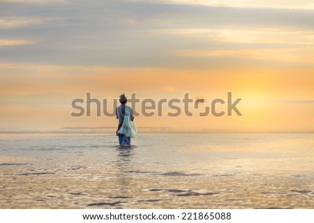 Lone fisherman on beach in the morning sunrise flare effect - stock photo