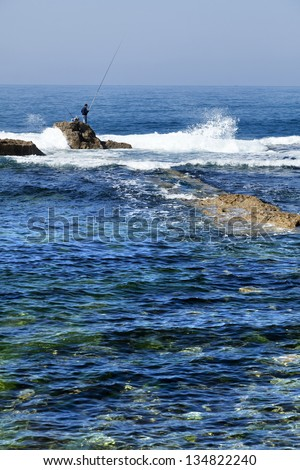 Lone fisherman standing on a large rock peeping out between the waves crashing against it, in the shallow waters next to the shore of the ancient city of Acco, Israel.