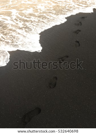 Lone footprints after walk on black sand beach by the ocean - Maui, Hawaii