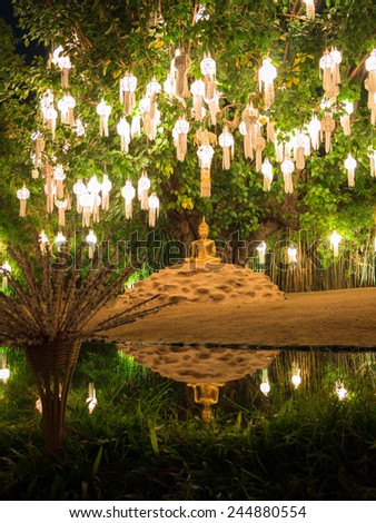 Lone golden Buddha sitting in the lotus position under a large tree with glowing lights - stock photo