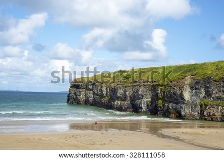 lone kayaker and tourist near the cliffs of ballybunion beach on the wild atlantic way ireland - stock photo