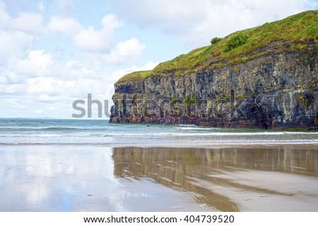 lone kayaker near the cliffs of ballybunion beach on the wild atlantic way ireland - stock photo