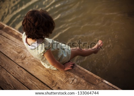 Lone little girl sitting on pier - stock photo