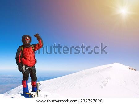 Lone male mountain climber on summit - stock photo