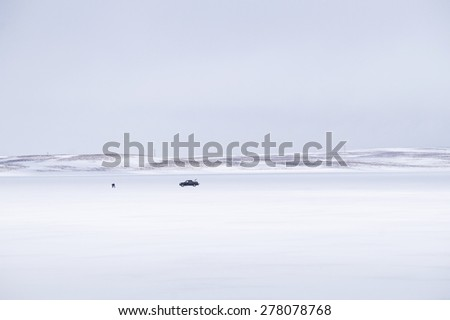 Lone man doing traditional fishing on frozen lake. Shot in Iceland.  - stock photo