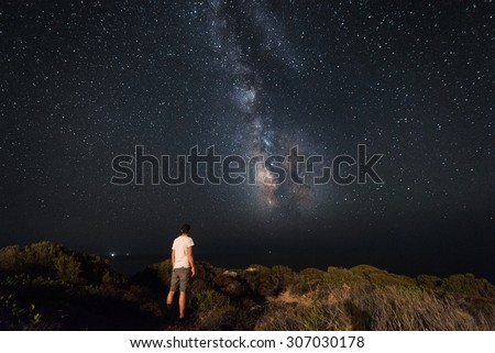 Lone man looks with amazement at the night sky with the Milky Way - horizzontal version - stock photo