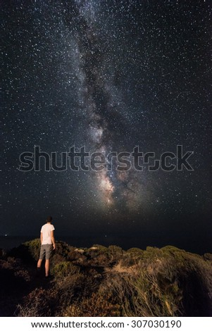 Lone man looks with amazement at the night sky with the Milky Way - vertical version - stock photo