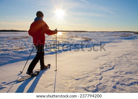 Lone man show shoeing in the snow. - stock photo