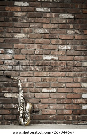 Lone old saxophone leans against brick wall outside abandoned jazz club