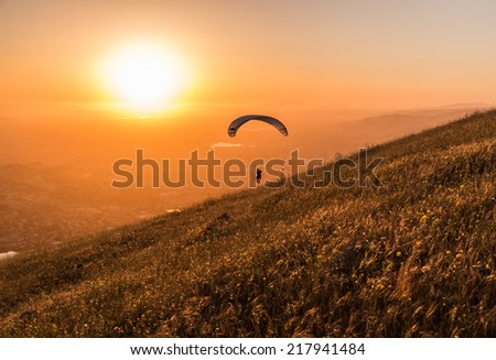 Lone paraglider drifts in the air right before the sunset - stock photo