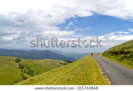 Lone pilgrim walking the Camino de Santiago through the Pyrenees - stock photo