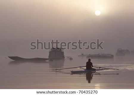 Lone rower passing silhouetted boats on the river Thames