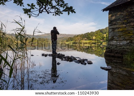 Lone silhouette, Rydal Water boat shed in the English Lake District - stock photo
