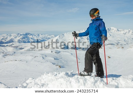 Lone skier in helmet enjoying the view over the beautiful landscape of winter mountains  - stock photo
