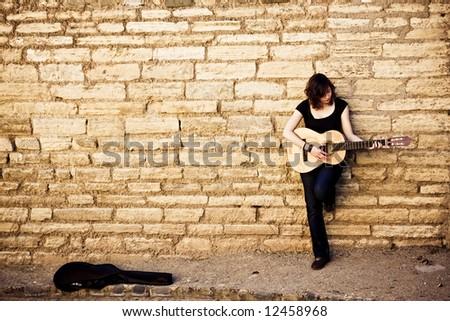 Lone street artist against stonewall as background - stock photo