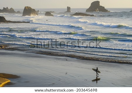 Lone Surfer carrying board along rugged Northern Oregon Pacific Coastline. - stock photo