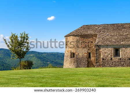 Lone tree and old stone church on green lawn under blue sky in Piedmont, Northern Italy. - stock photo